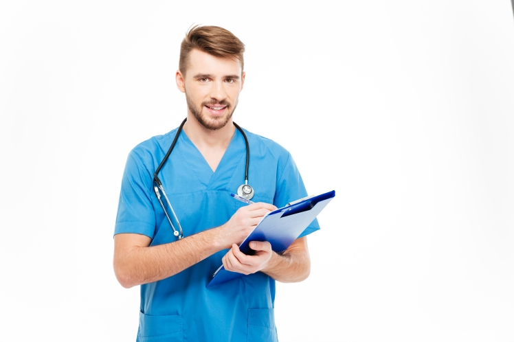 Smiling male doctor standing with clipboard
