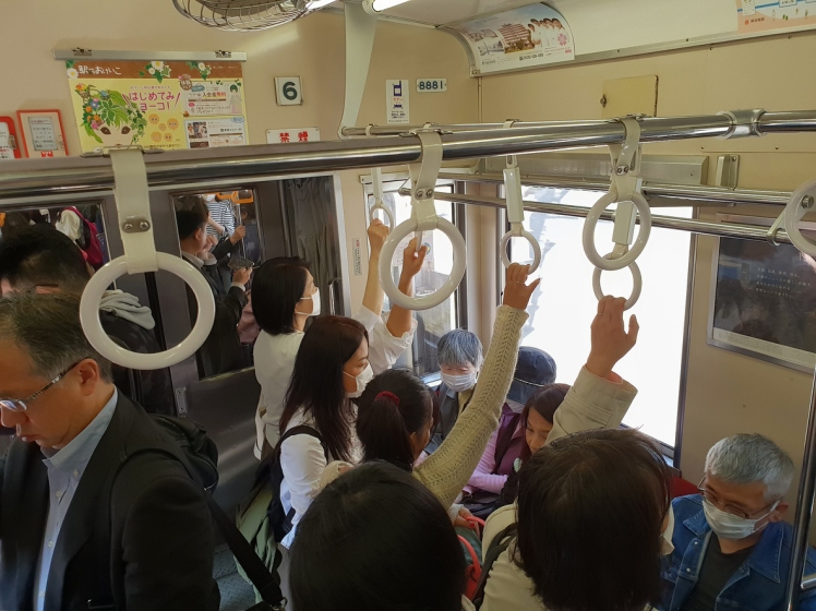 People traveling on the crowded Tokyo Metro underground subway train.