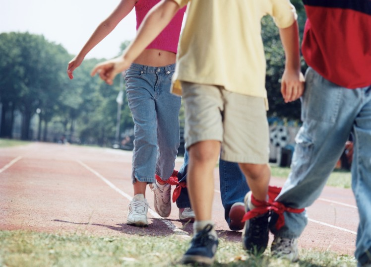 CHILDREN (9-11) IN THREE-LEGGED RACE, CLOSE-UP